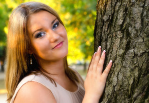 Beautiful girl leaning against a tree in the fall